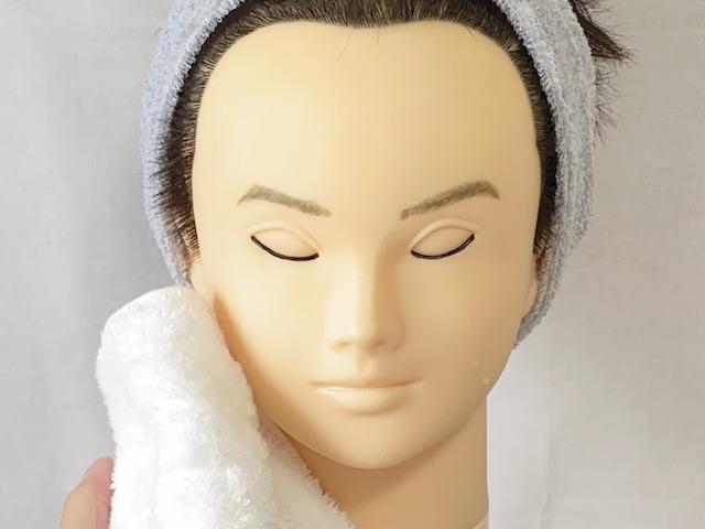 洗顔後にタオルで顔を拭く男性